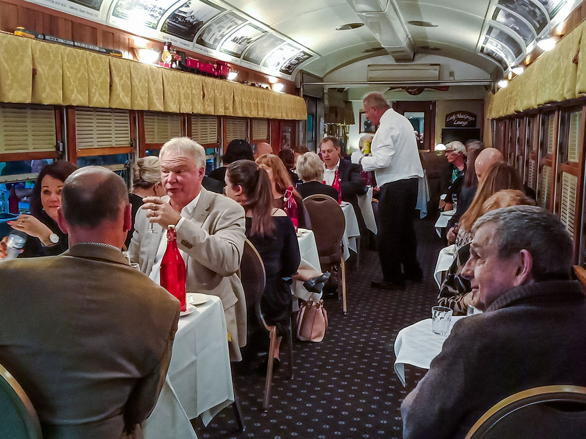 People sitting in old rail carriage at DownSteam Tourist Railway