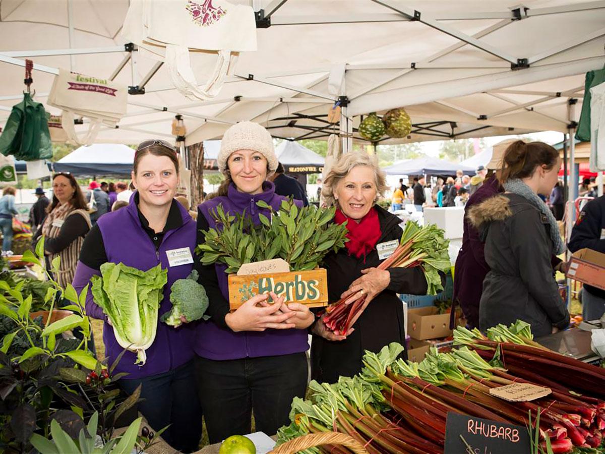 Ladies holding fresh produce at the Hamptons Festival Market