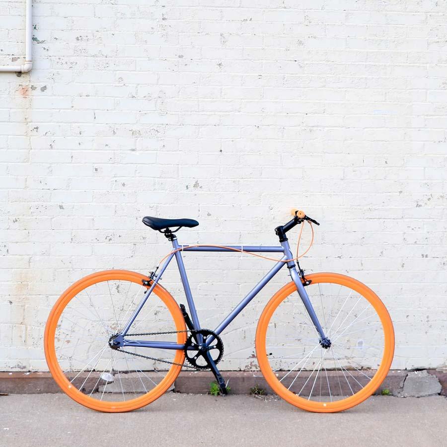 Bike with orange wheels leaning against white brick wall