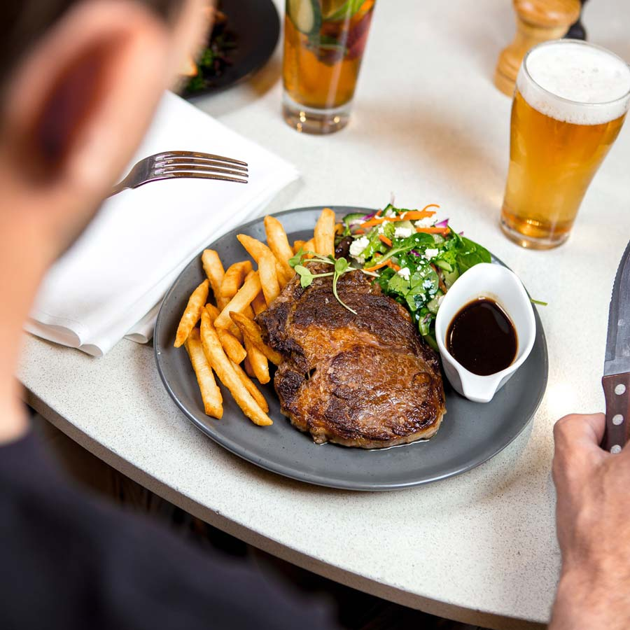 Man looking down at his steak, chips and salad with a beer