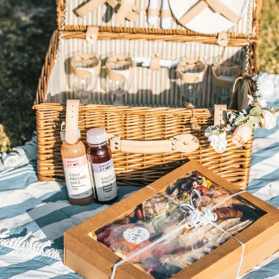 Picnic basket, coloured juices and assorted foods in a box on top of picnic blanket