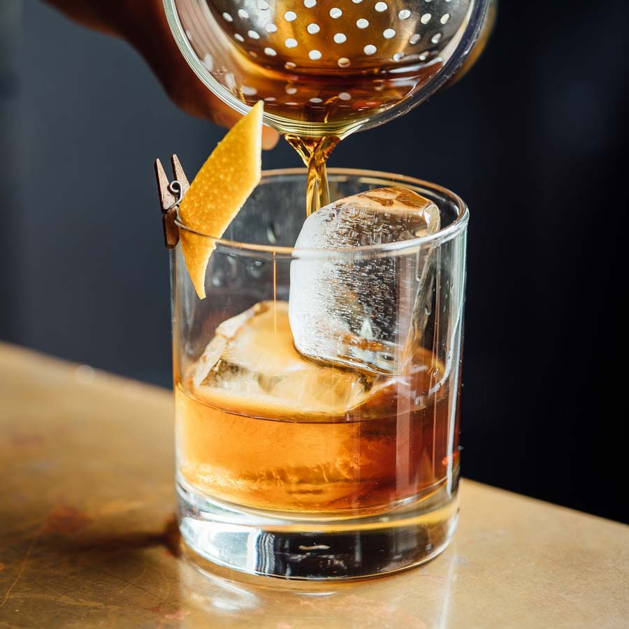 Pouring old fashioned into glass with ice and orange peel