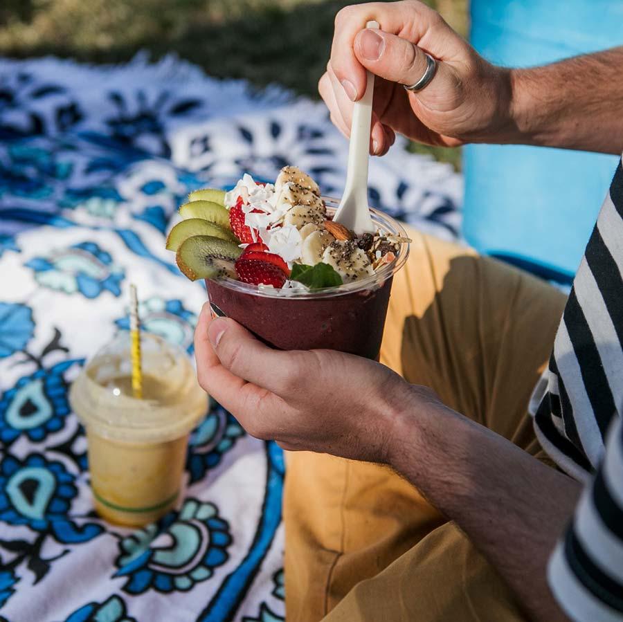 Man eating colourful Acia bowl on a picnic rug