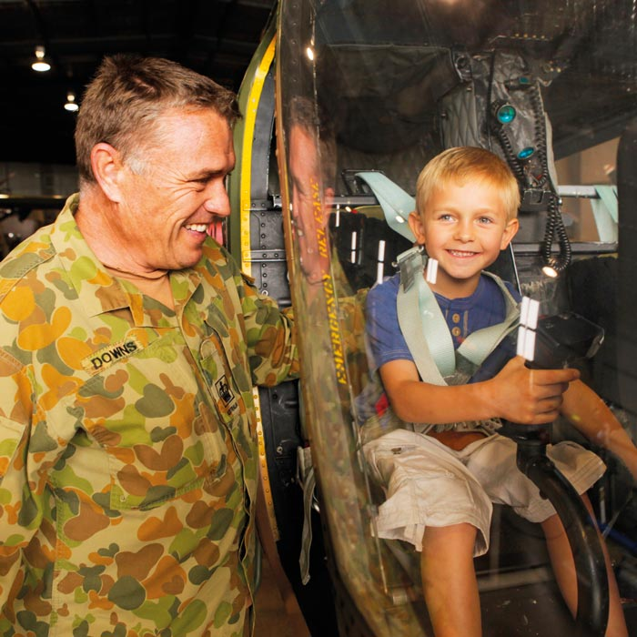 Little boy smiling inside of helicopter at Australian Army Flying Museum in Oakey