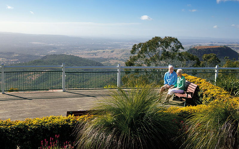 People sitting on bench seat at picnic point lookout