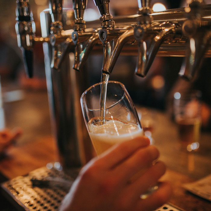 Beer frothing as it's poured into glass from tap