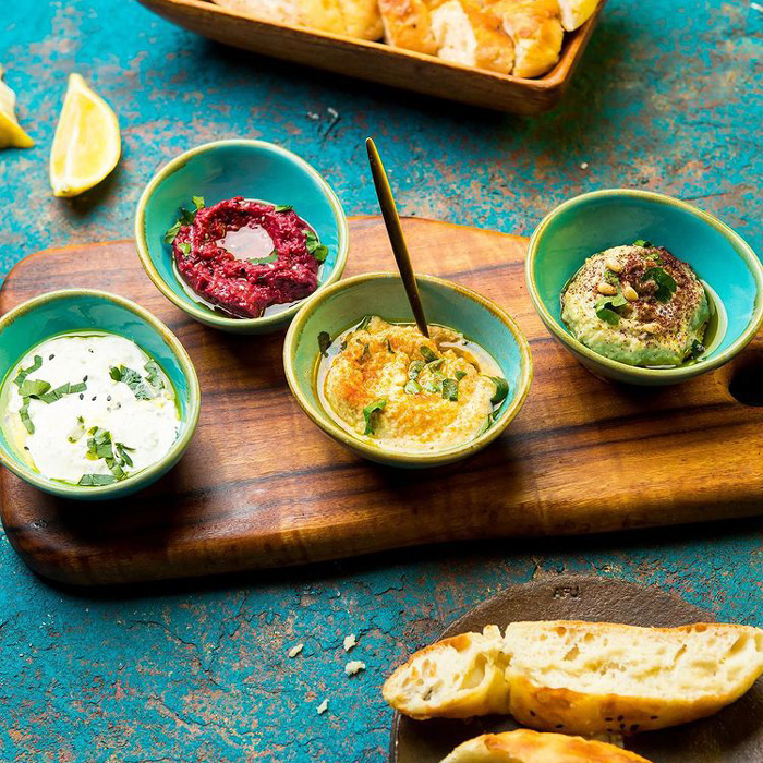 Bright coloured dips and bread on blue table