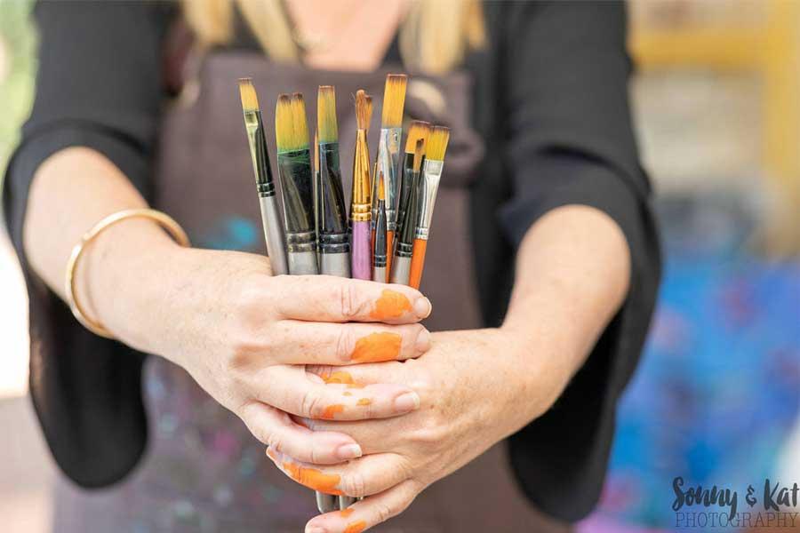 lady holding paintbrushes