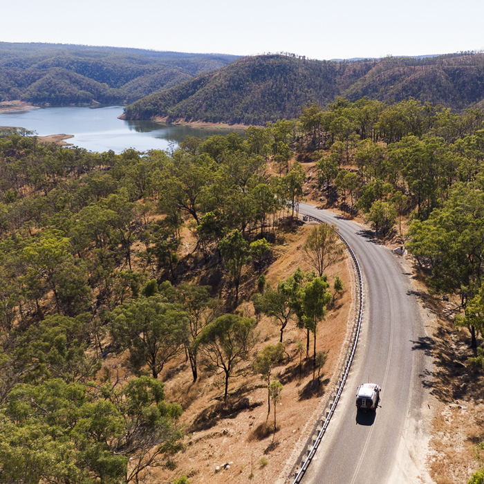 Aerial photo of car driving on winding road through bushland towards a lake